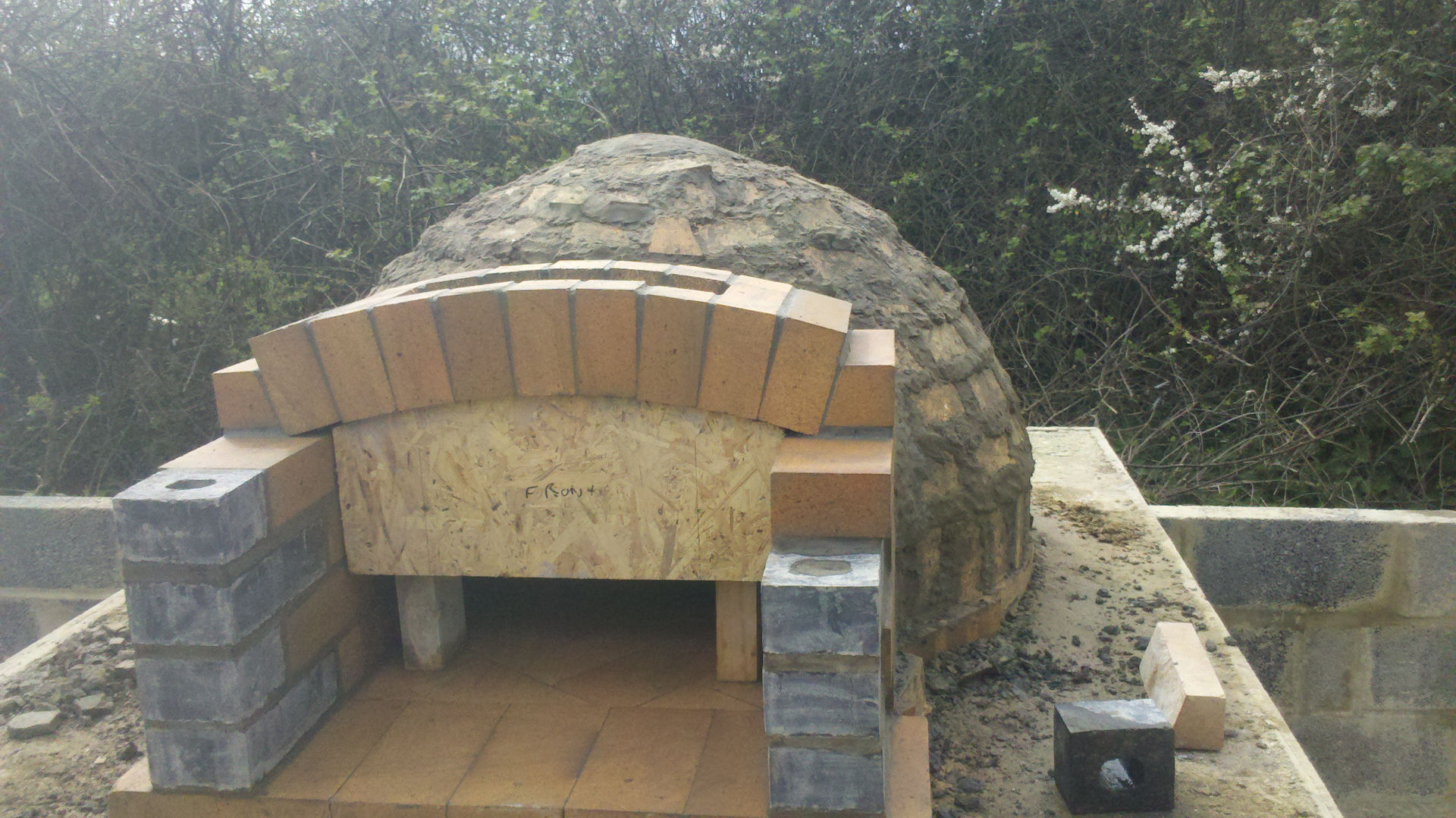 Wood-fired pizza oven archway over porch being installed